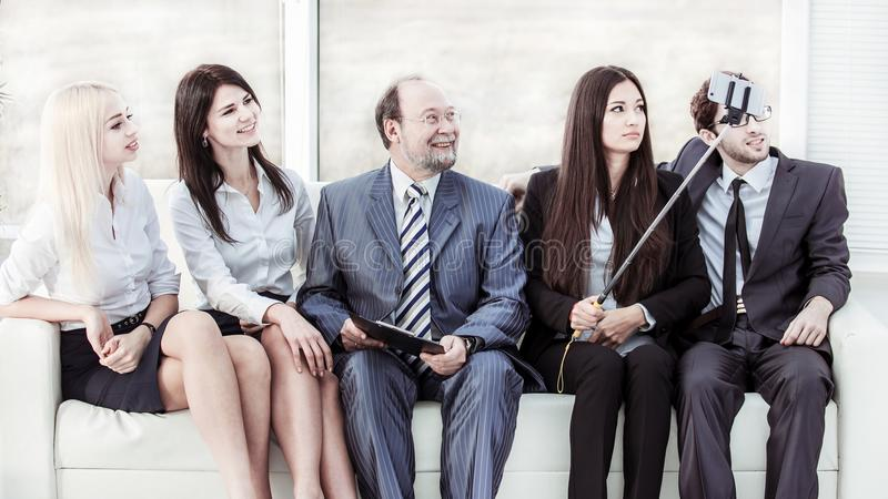Beautiful young woman employee makes a selfie with his boss and business team sitting near the window in the office. Young women employee makes a selfie with stock images
