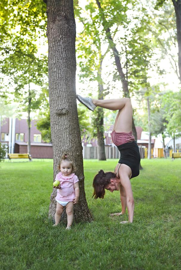 Young woman exercising with her baby in park royalty free stock photography