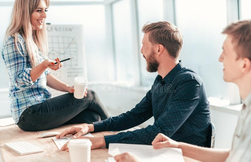 Young woman explaining to colleagues her ideas royalty free stock image