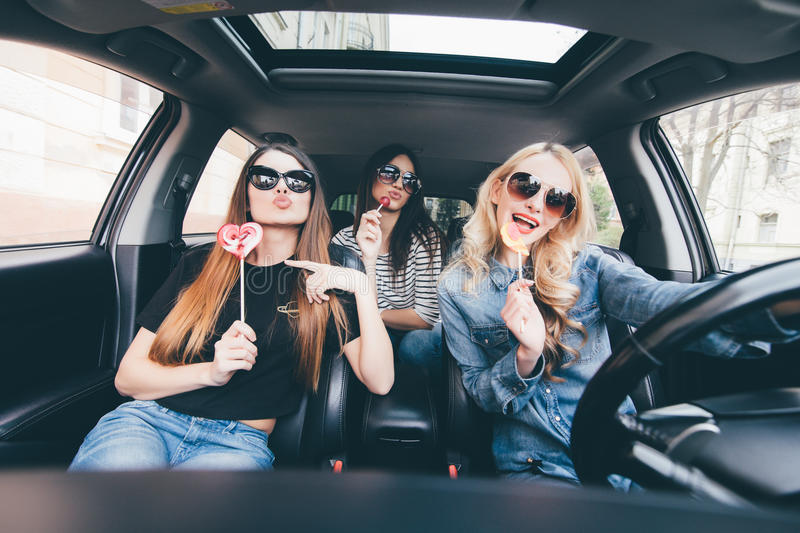 Young women friends with candy have fun when drive new car in road trip royalty free stock photos