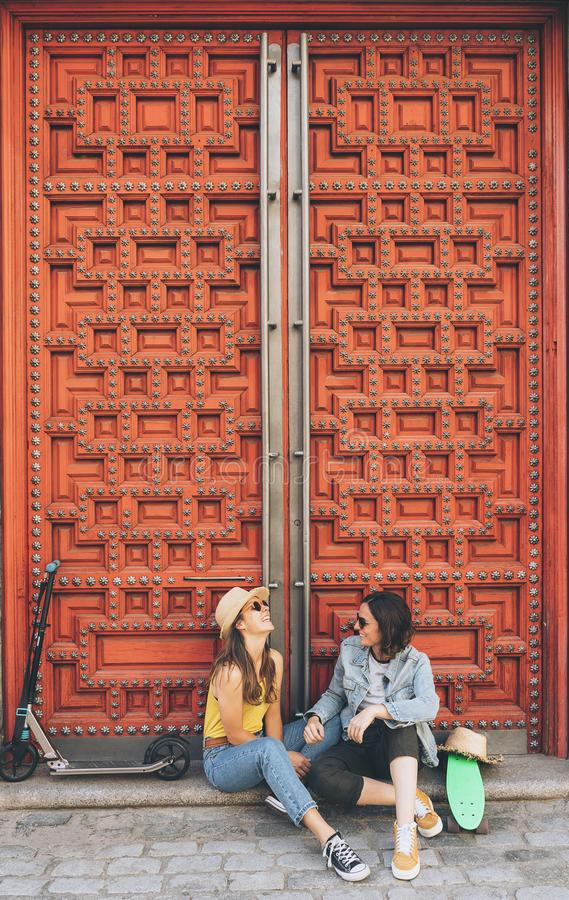 Young women gay couple looking and smiling each other in a red door background. Same sex happiness and joyful concept stock photos