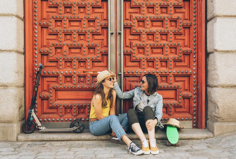 Young women gay couple looking and smiling each other in a red door background. Same sex happiness and joyful concept royalty free stock photos