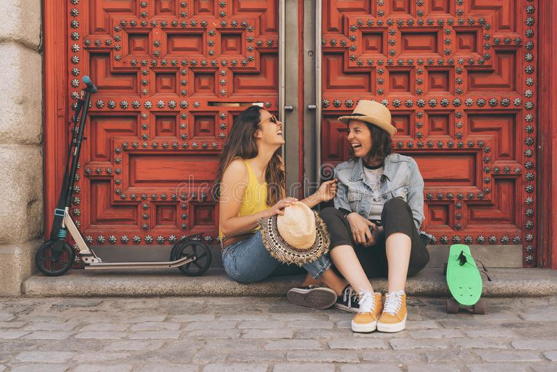 Young women gay couple looking and smiling each other in a red door background. Same sex happiness and joyful concept royalty free stock image