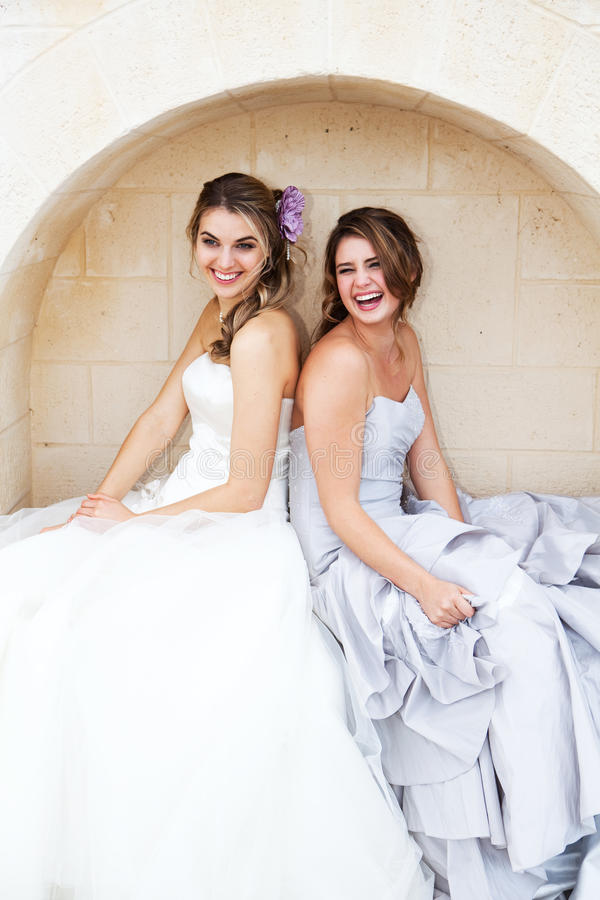 Young Women in Gowns and Sitting in an Alcove. Two attractive young women wearing formal dresses are smiling and sitting back to back in an alcove. Vertical shot stock images
