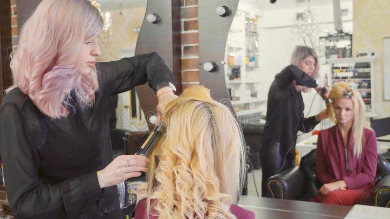Woman hairdresser making curls at blond hair with curling irons at beauty salon. stock photos