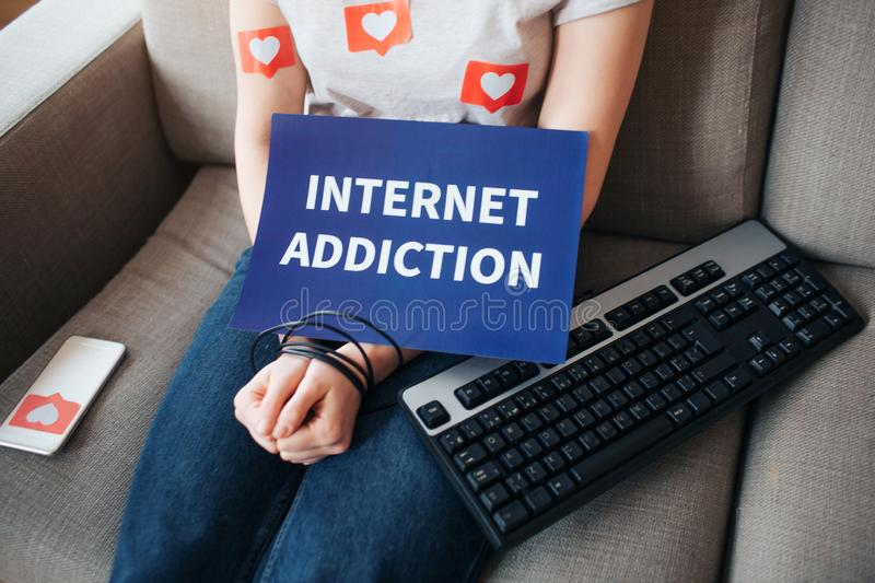 Young woman have social media addiction. Sitting on sofa. Hands are wrapped. Keyboard besides. Internet addiction. Cut stock images