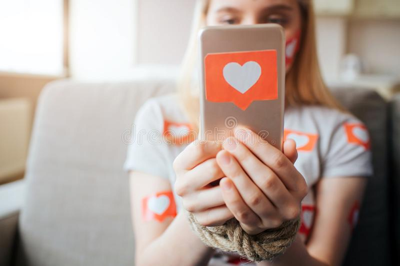 Young woman have social media addiction. Sitting on sofa and holding phone in hands. Like symbol. Heart shape. Daylight. Young women have social media addiction stock photos