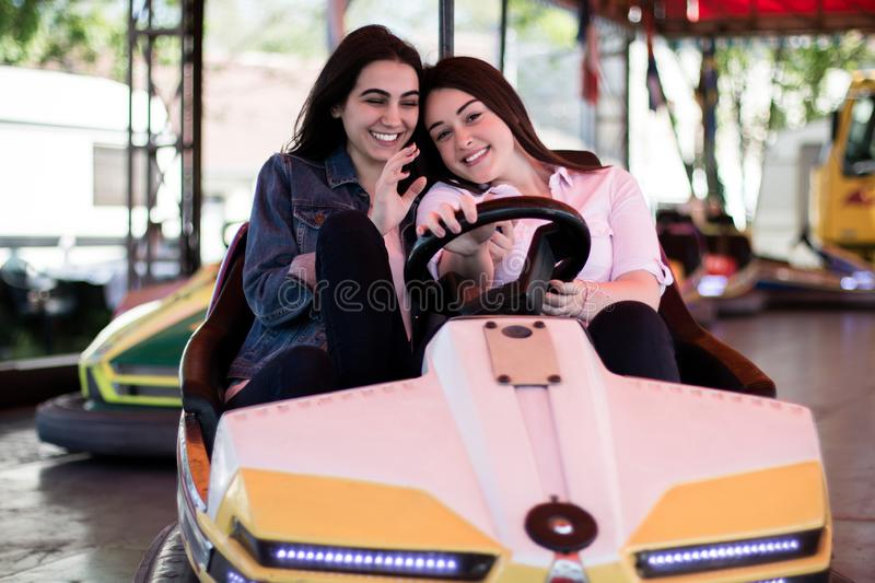 Young women having a bumper car ride. Two young cool women having a fun bumper car ride at the amusement park. Enjoying friendship royalty free stock images