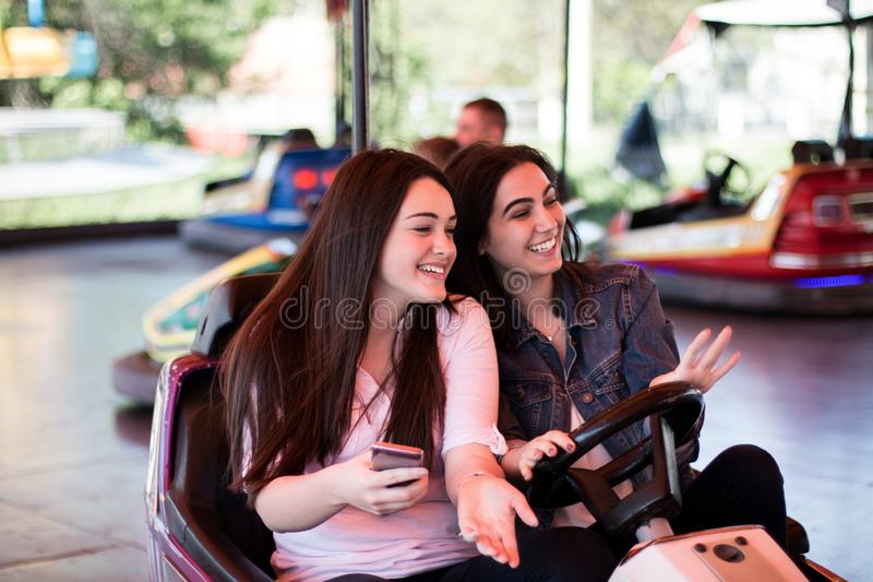 Young women having a bumper car ride. Two young women having a fun bumper car ride at the amusement park, laughing, enjoying themselves stock image