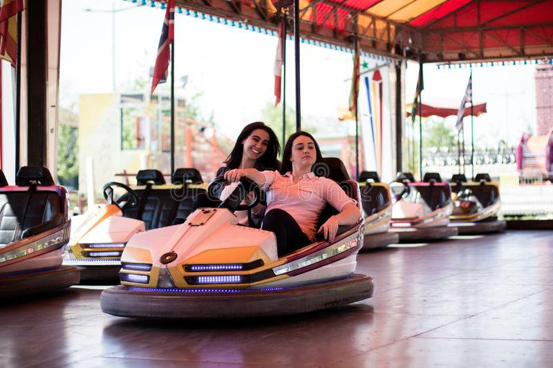 Young women having a bumper car ride. Two young women having a fun bumper car ride at the amusement park, laughing, enjoying themselves stock photos