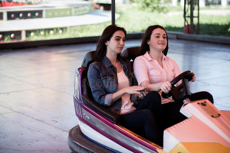 Young women having a bumper car ride. Two young cool women having a fun bumper car ride at the amusement park. Enjoying friendship stock images