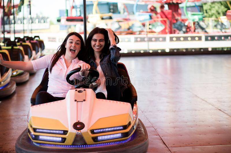 Young women having a bumper car ride. Two young women having a fun bumper car ride at the amusement park, laughing, enjoying themselves stock images