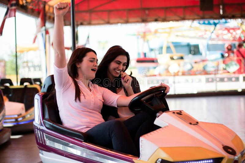 Young women having a bumper car ride. Two young women having a fun bumper car ride at the amusement park, laughing, enjoying themselves stock photography