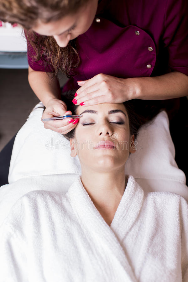 Cosmetic treatment. Young women having a cosmetic treatment stock images