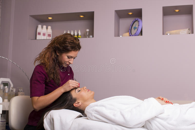 Young women having a cosmetic treatment royalty free stock image