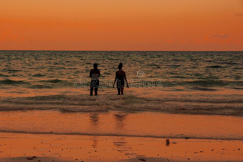 Young Women having fun at the beach. Young Women having fun against a golden sunset at Uroa Bay, Uroa Beach, Zanzibar  happy happiness active outdoors travel royalty free stock photo