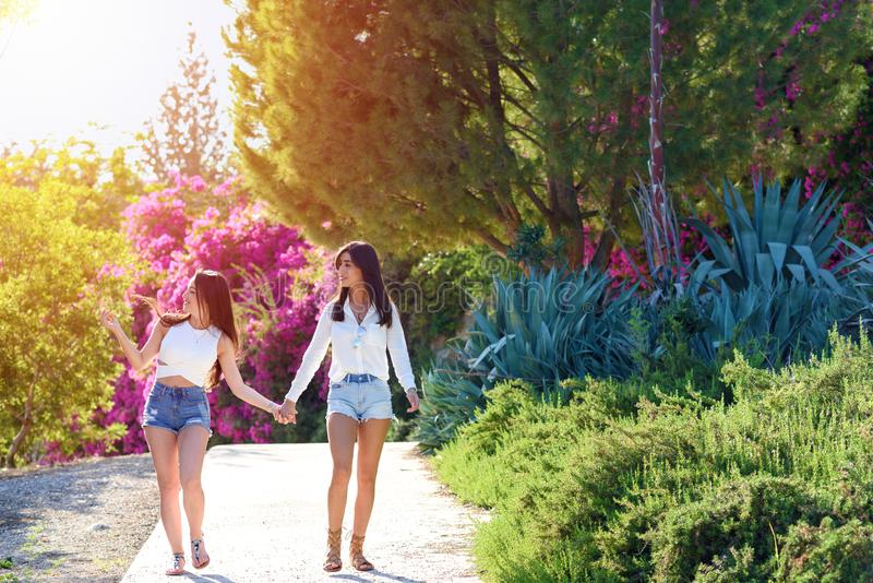 Beautiful happy young women holding hands on colorful natural background of bright pink flowers. Young women are having fun on the nature in sunny day.Two stock photography