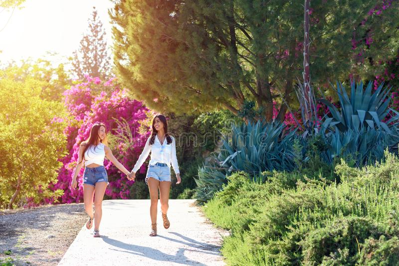 Beautiful happy young women holding hands on colorful natural background of bright pink flowers. Young women are having fun on the nature in sunny day.Two royalty free stock image