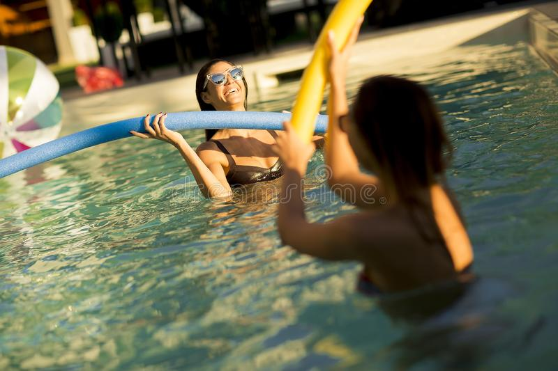 Young women having fun with swimming pool noodles stock photos