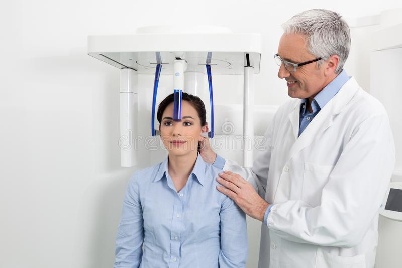 A dentist with his patient doing an x-ray panoramic digital. Young women having panoramic digital x-ray of her teeth with a middle age doctor in the dental stock photo