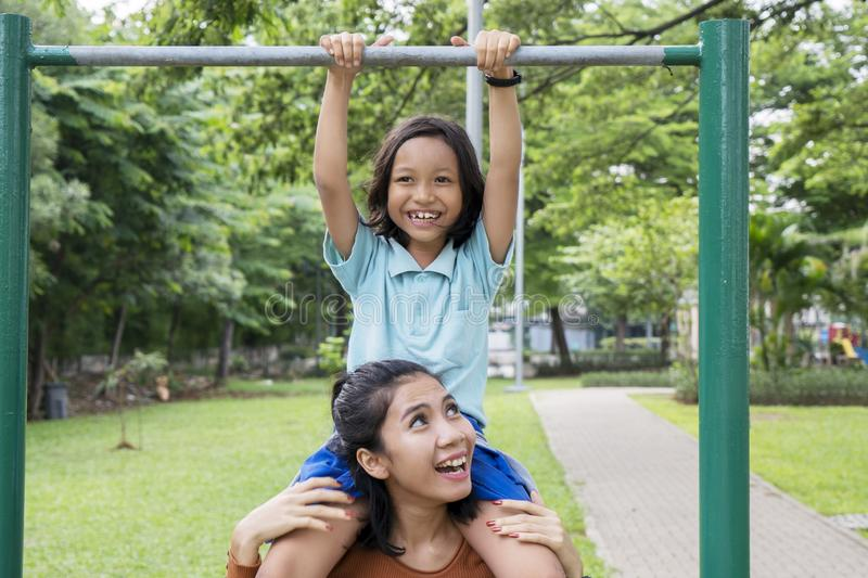 Woman helps her daughter to do pull up exercises stock images
