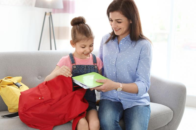 Young woman helping her little child get ready. Young women helping her little child get ready for school at home stock photos
