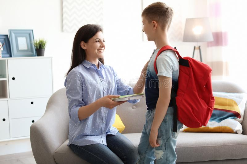 Young woman helping her little child get ready for school. Young women helping her little child get ready for school at home stock photography