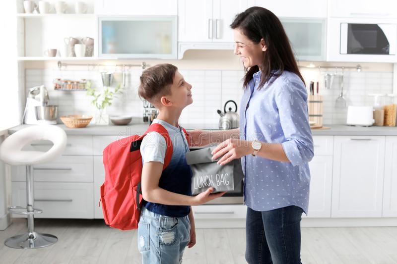 Young woman helping her little child get ready for school. Young women helping her little child get ready for school at home stock image