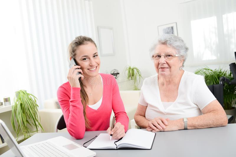 Young woman helping an old senior woman doing paperwork and administrative procedures with laptop computer at home. Young women helping an old senior women doing royalty free stock image