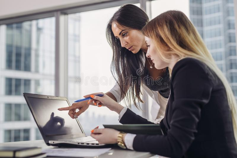 Young woman helping student explaining information pointing at screen of laptop during IT course in classroom. Young women helping student explaining information stock photography