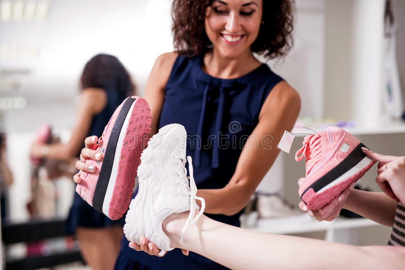 Young women helping their friend to choose sports footwear comparing the soles of new and old shoes in fashion showroom royalty free stock photos