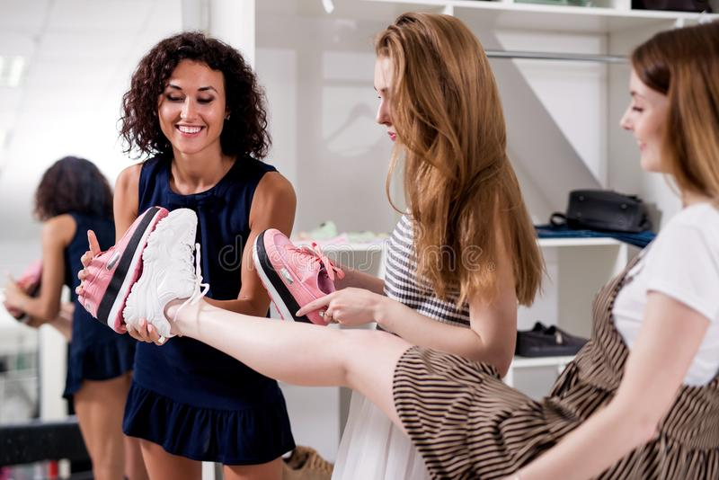 Young women helping their friend to choose sports footwear comparing the soles of new and old shoes in fashion showroom.  stock images