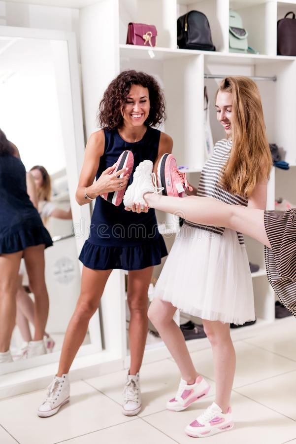 Young women helping their friend to choose sports footwear comparing the soles of new and old shoes in fashion showroom.  stock photos