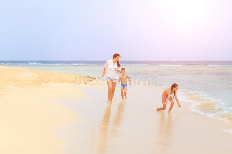 Young woman with children enjoying beach vacation. Young women with her children enjoying beach vacation. Family traveling concept background royalty free stock images