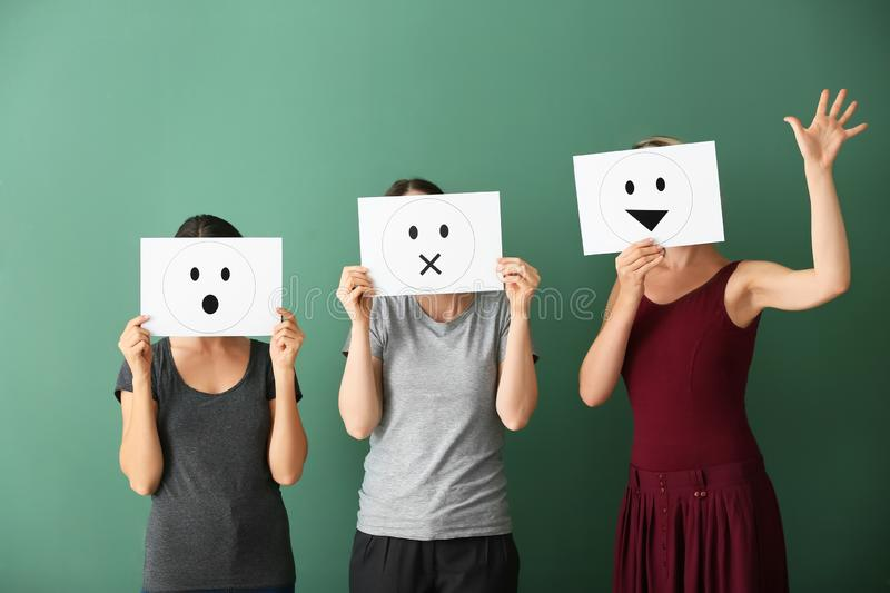 Young women hiding faces behind sheets of paper with drawn emoticons on color background royalty free stock photo