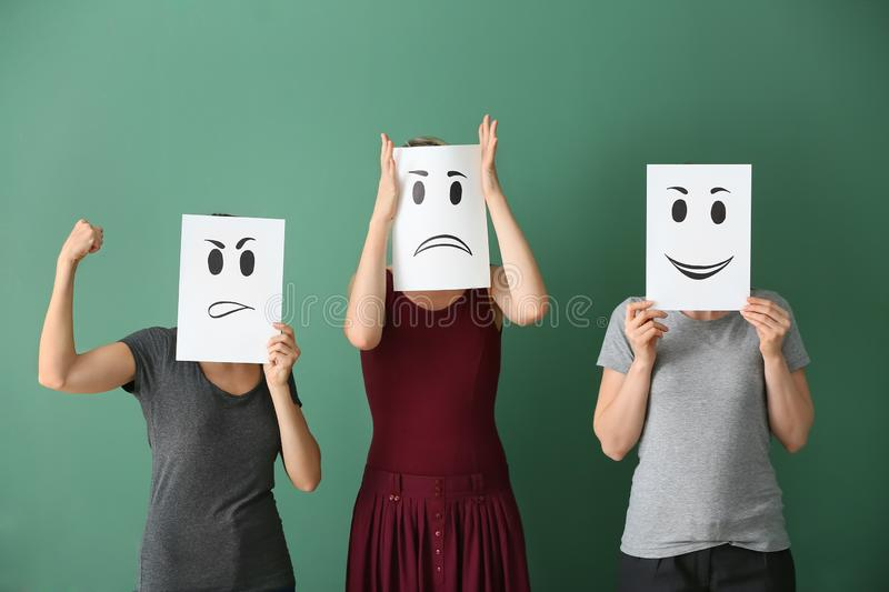 Young women hiding faces behind sheets of paper with drawn emoticons on color background stock images