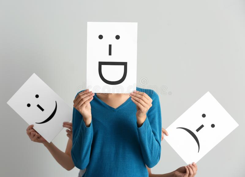 Young women hiding faces behind sheets of paper with drawn emoticons on light background stock images