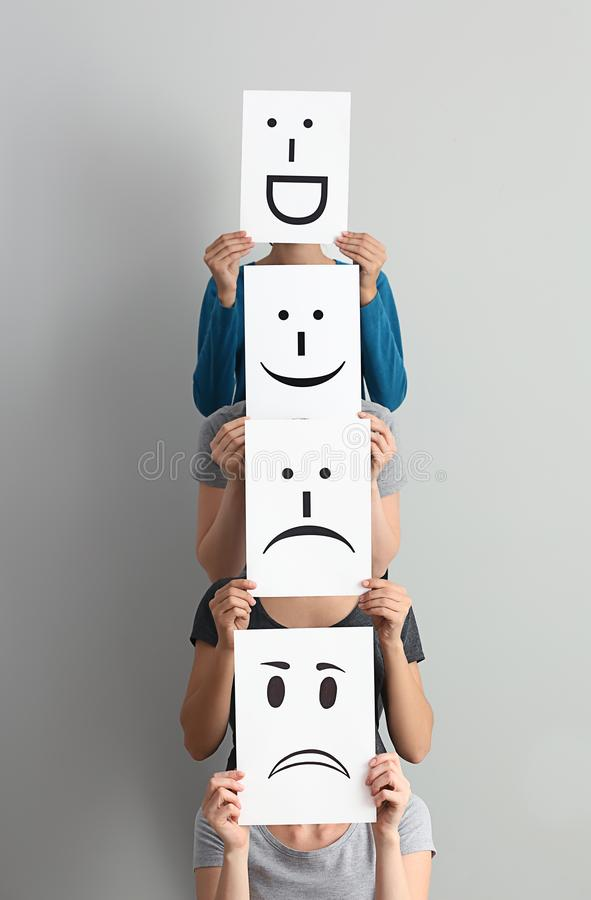 Young women hiding faces behind sheets of paper with drawn emoticons on light background royalty free stock photo