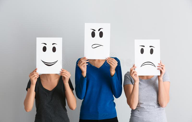 Young women hiding faces behind sheets of paper with drawn emoticons on light background stock photos