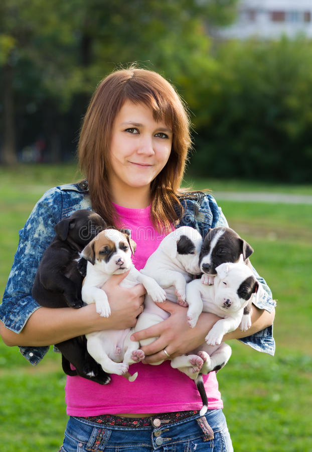 Young Women Holding Five Puppies Royalty Free Stock Photos