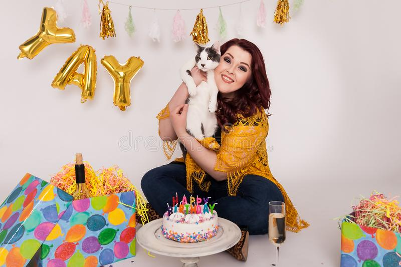 Young women holding gray and white cat Happy Birthday themed studio set stock photo