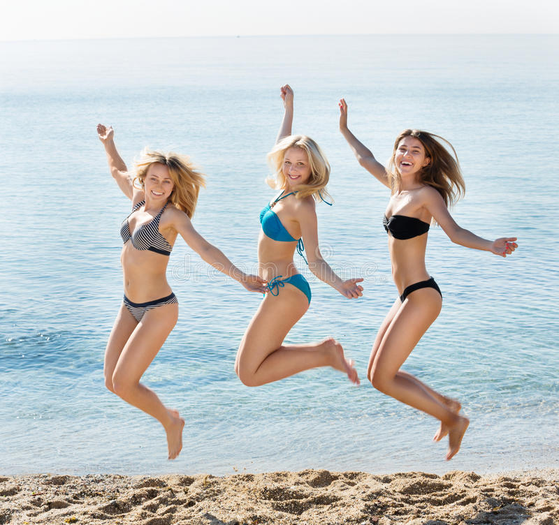 Young women hopping on beach stock images