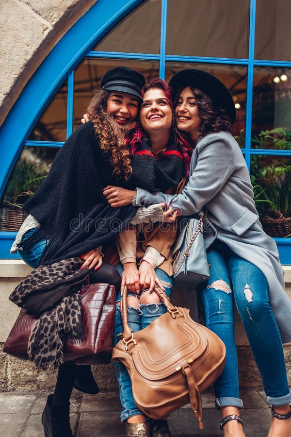 Young women hugging and laughing on city street. Best friends having good time together stock photography