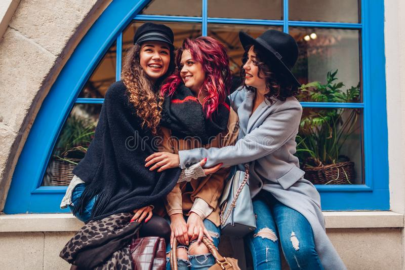 Young women hugging and laughing on city street. Best friends having good time together royalty free stock photos