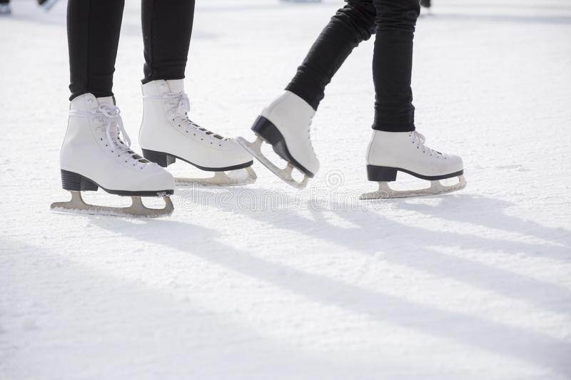 Women ice skating on ice rink. Young women ice skating on ice rink, close-up on skates royalty free stock photo