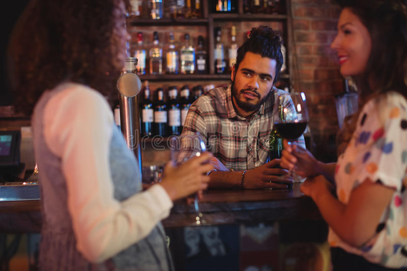 Young women interacting with bartender at counter royalty free stock image