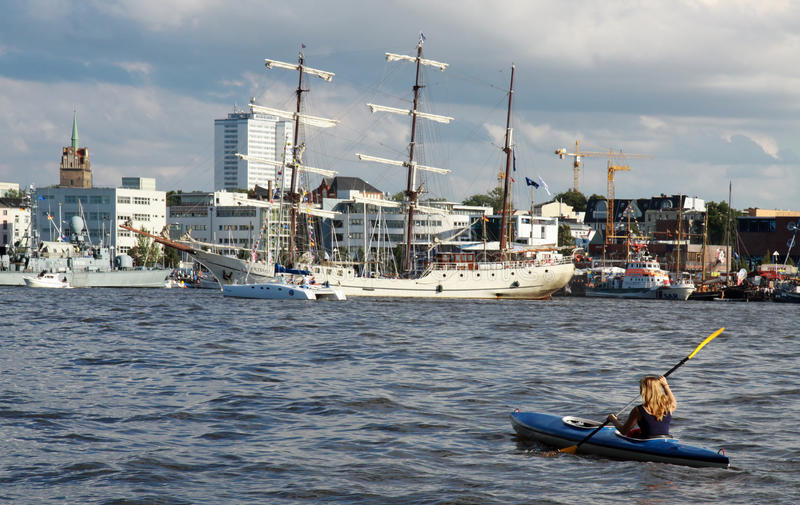 Young women with kayak in front of a sailing ship stock photography