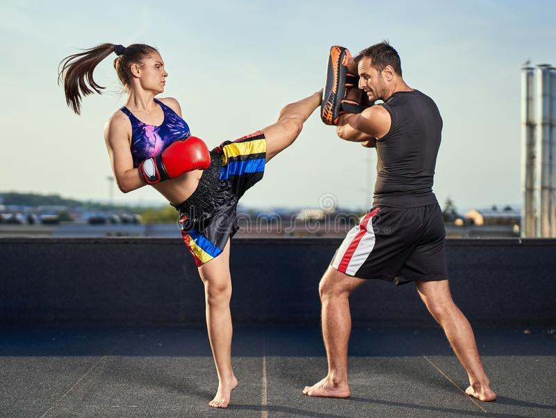 Young woman kickboxer in urban environment, training. Young women kickbox fighter training with her coach on the roof above the city stock photography