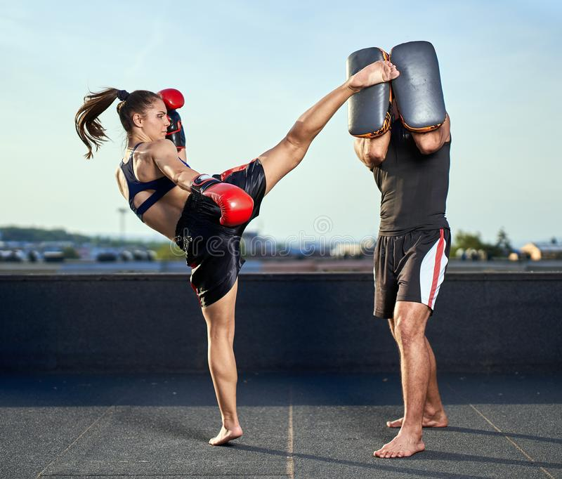 Young woman kickboxer in urban environment, training. Young women kickbox fighter training with her coach on the roof above the city royalty free stock images