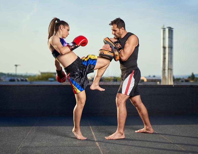 Young woman kickboxer in urban environment, training. Young women kickbox fighter training with her coach on the roof above the city stock images